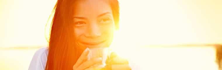 femme asiatique boit verre lumiere soleil