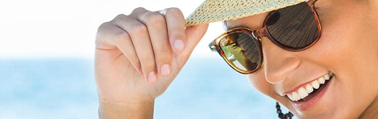 femme portant lunettes soleil chapeau plage