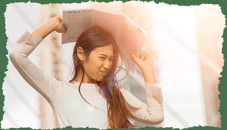 femme asiatique eblouie soleil journal visage