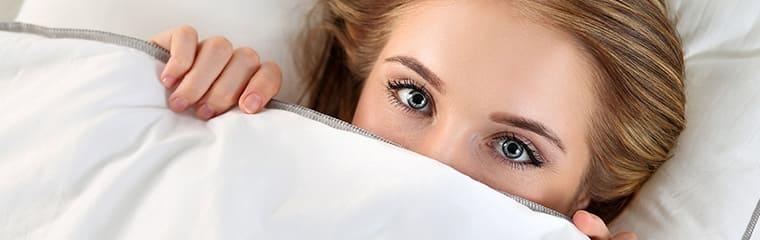 femme couchée sous couette yeux bleu